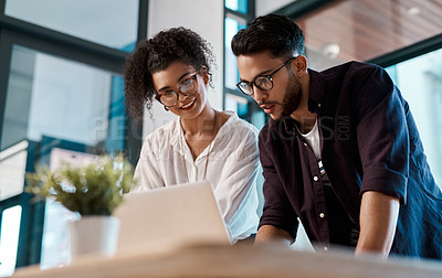 Buy stock photo Cropped shot of two young business colleagues standing together and using a laptop in the office