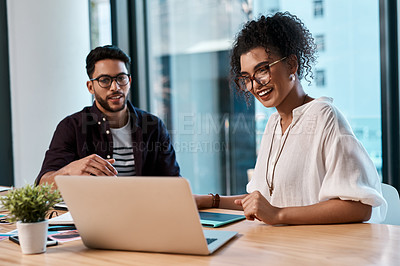 Buy stock photo Cropped shot of two young business colleagues sitting together and looking at a laptop in the office