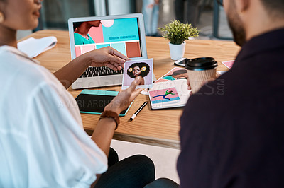 Buy stock photo Cropped shot of two young businesspeople sitting together and having a discussion over polaroids in the office