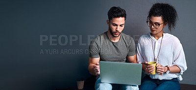Buy stock photo Cropped shot of two young business colleagues sitting against a gray background together and using a laptop
