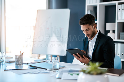 Buy stock photo Cropped shot of a handsome young businessman sitting alone and using a tablet in his office