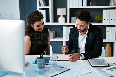Buy stock photo Cropped shot of two young businesspeople sitting together and reading notes while in the office