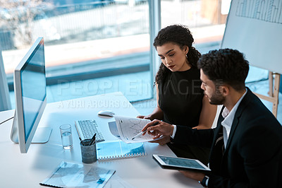 Buy stock photo Cropped shot of two young businesspeople sitting together in the office and using a tablet and paperwork during a discussion