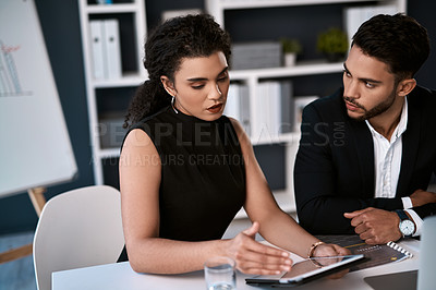 Buy stock photo Cropped shot of two young businesspeople sitting together and having a discussion while using a tablet in the office