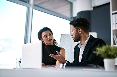 Buy stock photo Cropped shot of two young businesspeople sitting together and having a discussion while using a laptop in the office