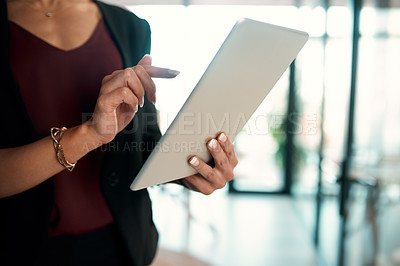Buy stock photo Cropped shot of an unrecognizable businesswoman standing in her office alone and using a tablet