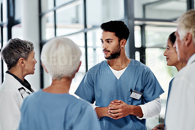 Buy stock photo Shot of a young medical practitioner having a discussion with his colleagues in a hospital