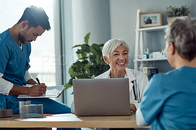 Buy stock photo Cropped shot of an attractive mature female doctor having a meeting with her colleagues in her office
