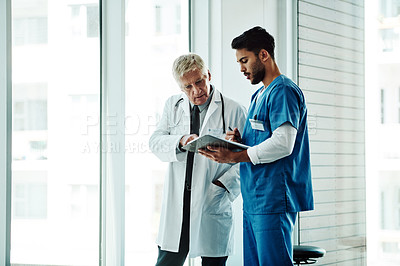 Buy stock photo Cropped shot of a handsome mature male doctor discussing a file with a young male nurse while standing in a hospital