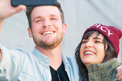 Buy stock photo Cropped shot of an affectionate young couple taking selfies together outdoors