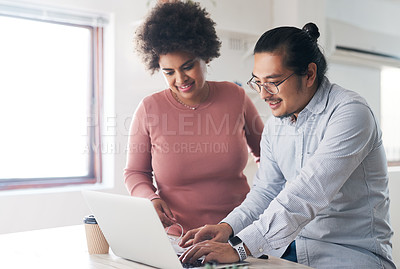 Buy stock photo Shot of a young businessman and businesswoman using a laptop in a modern office