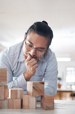 Buy stock photo Shot of a young businessman working with wooden building blocks in a modern office