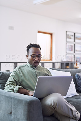 Buy stock photo Shot of a young businessman using a laptop on a sofa in a modern office
