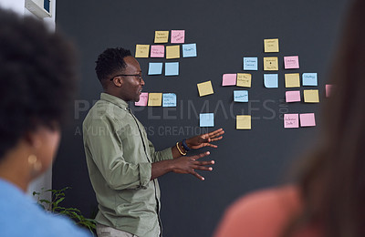 Buy stock photo Shot of a team of young businesspeople having a brainstorming session in a modern office