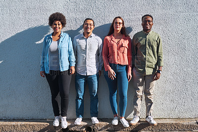 Buy stock photo Shot of a group of young people standing together against an urban background outdoors