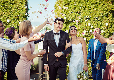Buy stock photo Shot of a happy young couple getting showered with flower petals after getting married in a garden
