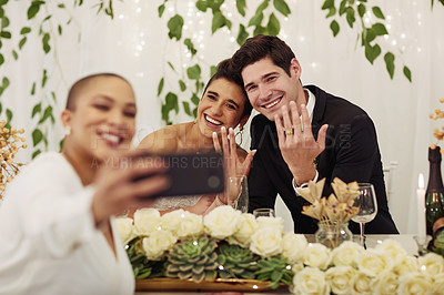 Buy stock photo Shot of a young woman taking a selfie with the bride and groom at their wedding reception
