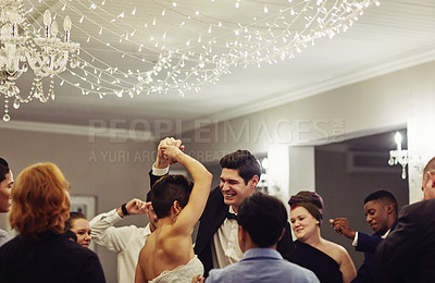 Buy stock photo Shot of a young couple dancing with their friends at their wedding reception
