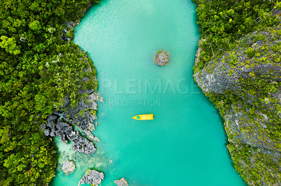 Buy stock photo High angle shot of a boat sailing through a canal running along the Raja Ampat Islands in Indonesia