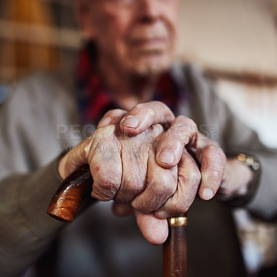 Buy stock photo Cropped shot of an unrecognizable senior man leaning on his walking stick at home