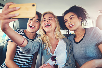 Buy stock photo Cropped shot of young women taking a selfie while out on a road trip together