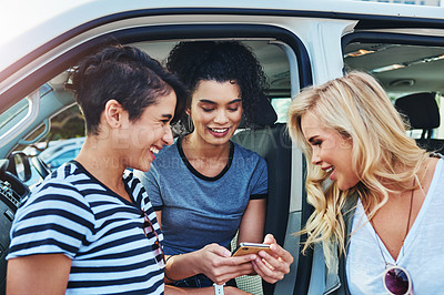 Buy stock photo Shot of friends looking at something on a cellphone while out on a road trip