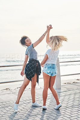 Buy stock photo Shot of two friends spending the day together on a sunny day