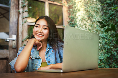 Buy stock photo Portrait of an attractive young woman using her laptop while relaxing at an outdoor cafe