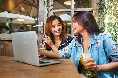 Buy stock photo Shot of two attractive young women using a laptop while having drinks and relaxing together at an outdoor cafe