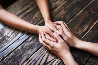 Buy stock photo Cropped shot of two unrecognizable women holding hands in comfort on a table outdoors