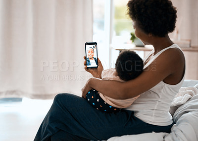 Buy stock photo Shot of a mother holding her infant daughter and video calling her husband with a cellphone at home