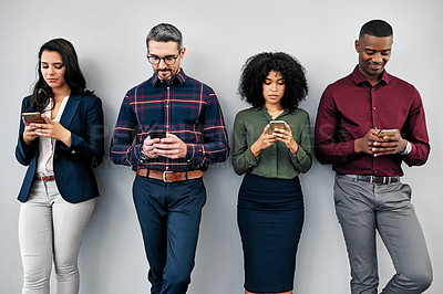 Buy stock photo Studio shot of a group of businesspeople using their smartphones while waiting in line against a grey background