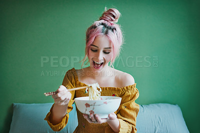Buy stock photo Shot of an attractive young woman eating a bowl of pasta while relaxing in her bedroom at home