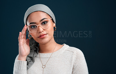 Buy stock photo Cropped shot of an attractive young woman standing against a black background alone while wearing spectacles and a headscarf