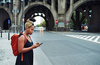 Buy stock photo Cropped shot of an attractive young woman standing on the street alone and using her cellphone