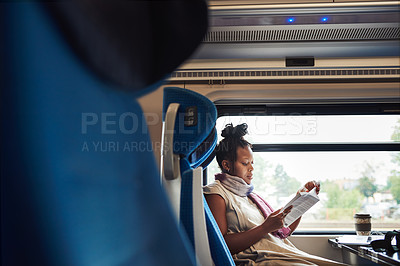Buy stock photo Cropped shot of an attractive young woman sitting alone in a train and reading a book during a trip
