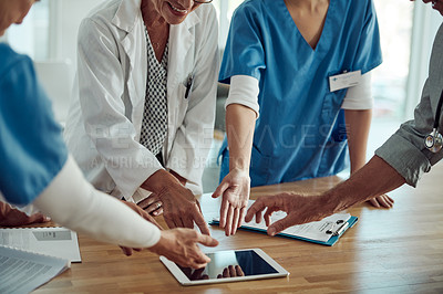 Buy stock photo Cropped shot of a group of unrecognizable doctors about to tap on a digital tablet inside of a doctor's office