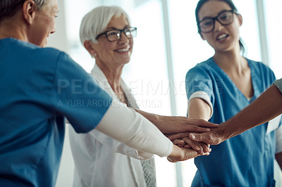 Buy stock photo Cropped shot of a group of confident doctors making a huddle with their hands inside of a doctor's office