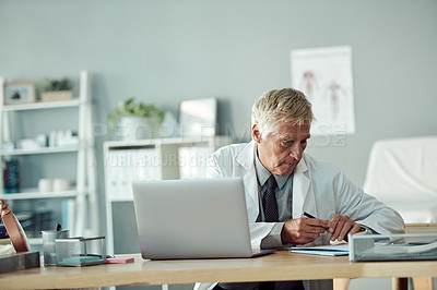 Buy stock photo Cropped shot of a mature male doctor filling in a form while being seated at his desk inside of a doctor's office during the day