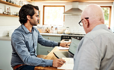 Buy stock photo Cropped shot of a handsome young businessman sitting with his senior client and using a laptop in an indoor meeting