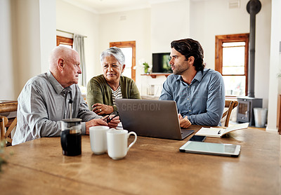 Buy stock photo Cropped shot of a young financial advisor sitting with his senior clients in their home for financial planning