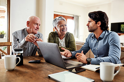 Buy stock photo Cropped shot of a handsome young businessman sitting with his senior clients in their home and discussing their finances