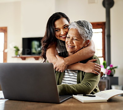 Buy stock photo Cropped shot of an attractive young woman hugging her grandmother before helping her with her finances on a laptop