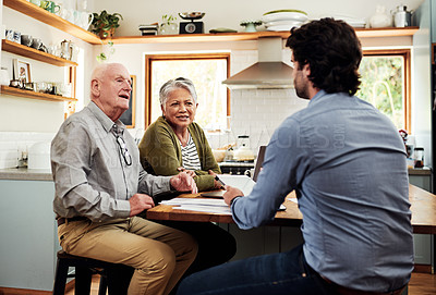 Buy stock photo Cropped shot of a senior couple sitting and having a meeting with their financial advisor in their home
