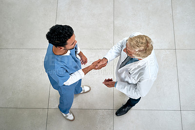 Buy stock photo High angle shot of two medical practitioners shaking hands in a hospital