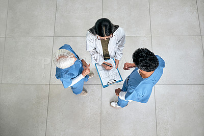 Buy stock photo High angle shot of a group of medical practitioners going through paperwork together in a hospital