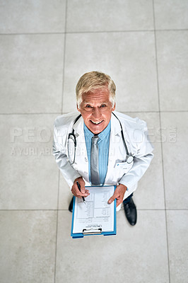 Buy stock photo Portrait of a senior doctor holding a clipboard in a hospital