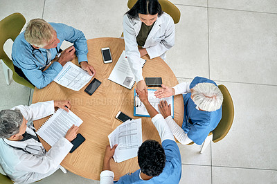 Buy stock photo High angle shot of medical practitioners shaking hands during a meeting in a hospital
