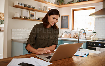 Buy stock photo Cropped shot of an attractive young woman using a laptop while working from home