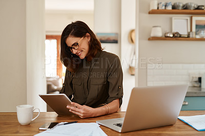 Buy stock photo Cropped shot of an attractive young woman smiling while using a digital tablet to work from home